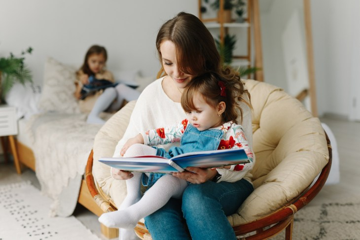 A mother is reading to her infant daughter.