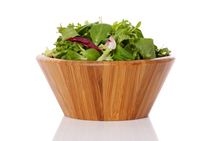 A wooden bowl with salad in it.