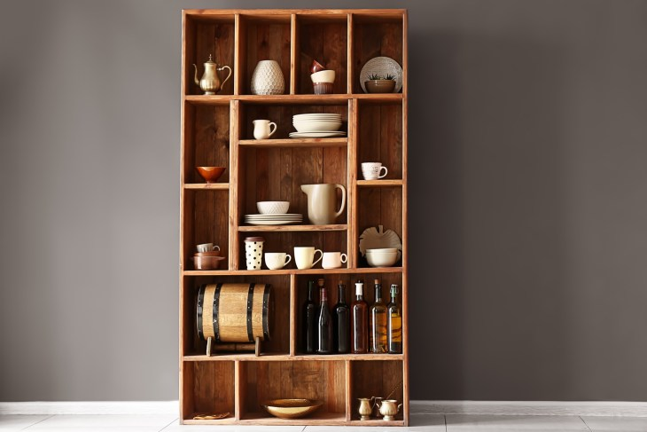 A brown cupboard with kitchen items inside.