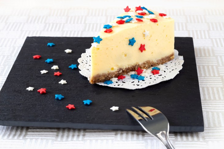 A cheesecake with red, white, and blue star-shaped sprinkles on top.