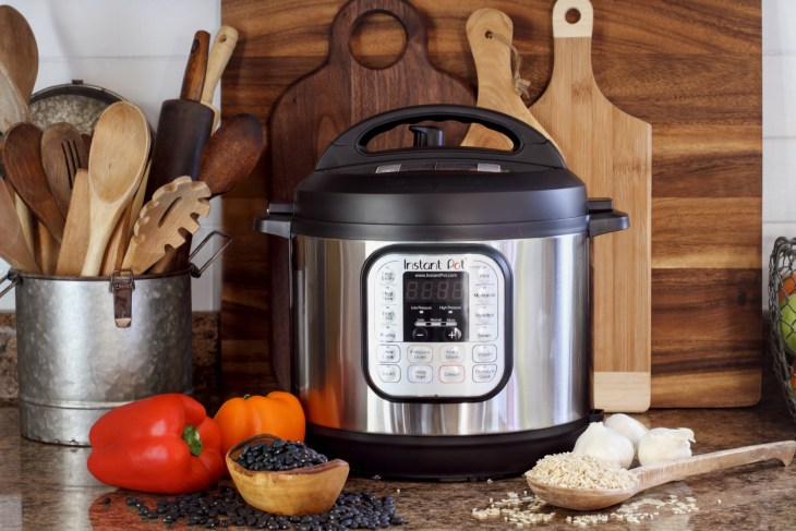 An instant pot on a table surrounded by kitchen items.