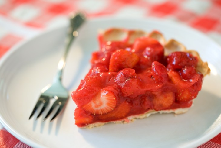 A piece of strawberry pie on a plate.
