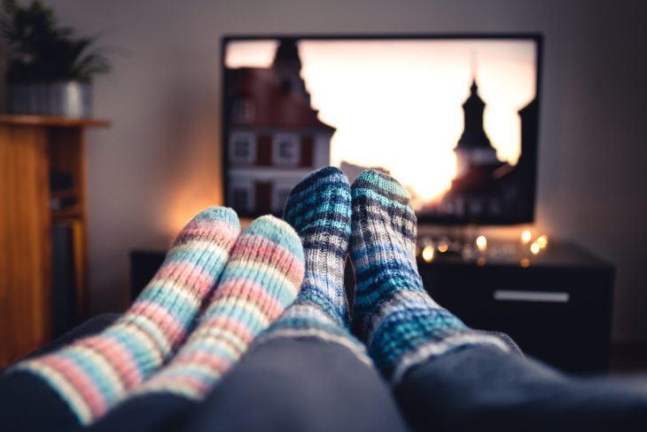 Legs with socks in front of a television.
