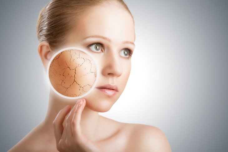 A woman touching her face with a blurb focusing on her dry skin.