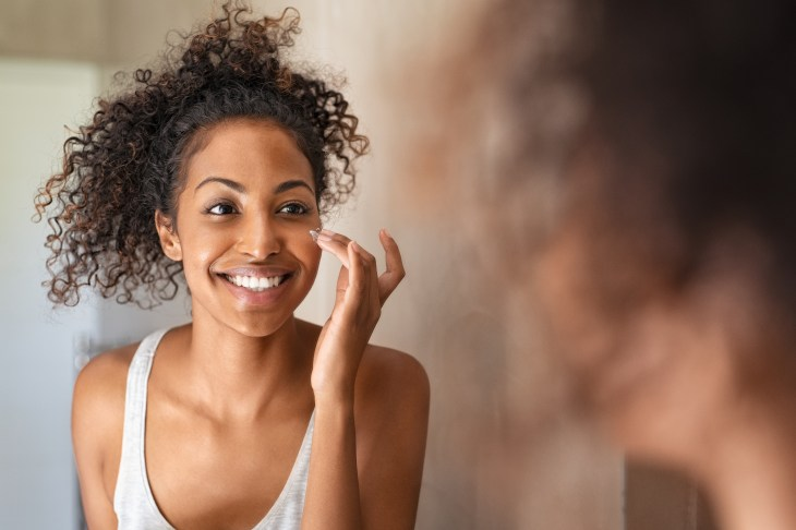 A girl looking into a mirror applying cream to her face.