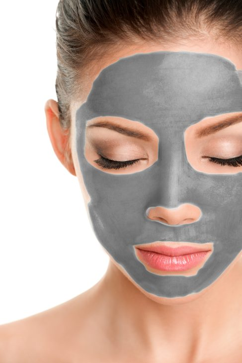 A woman's face with a clay grey mask on.