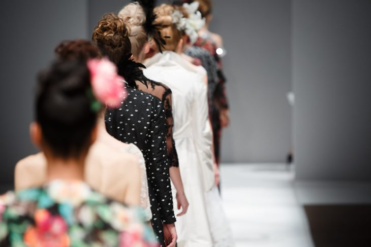 Back of heads of models lined up to walk a runway show.