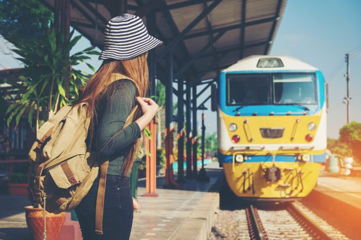 A Girl with a backpack standing on a train platform as a train approaches.