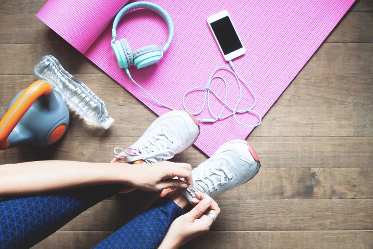 An unrolled yoga mat, phone with headphones, kettle bell and person tying their shoes.