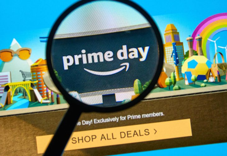 A black magnifying glass over the logo of Amazon Prime Day website where a person can shop online deals.
