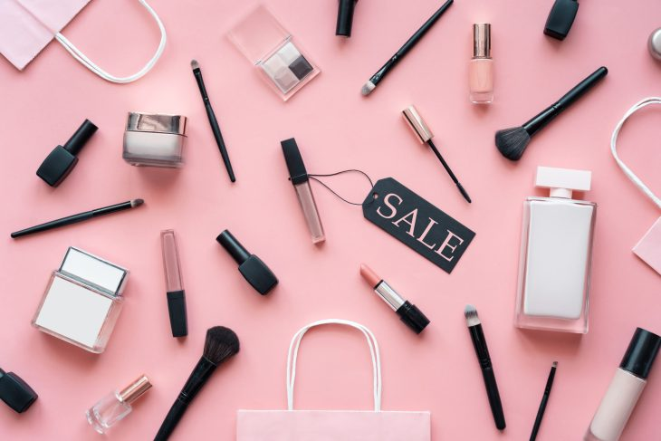 Cosmetic and perfume female products accessories promotion offer with sale tag beauty makeup fashion items objects set with shopping bags on pink table background