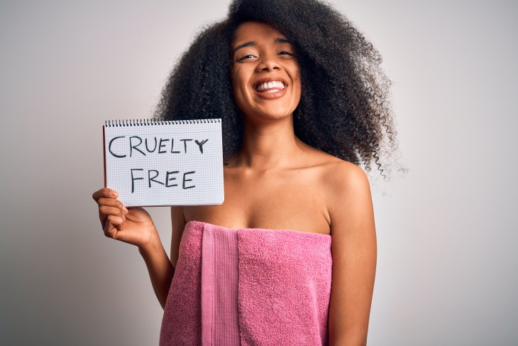 A woman in a towel holding a cruelty free sign.