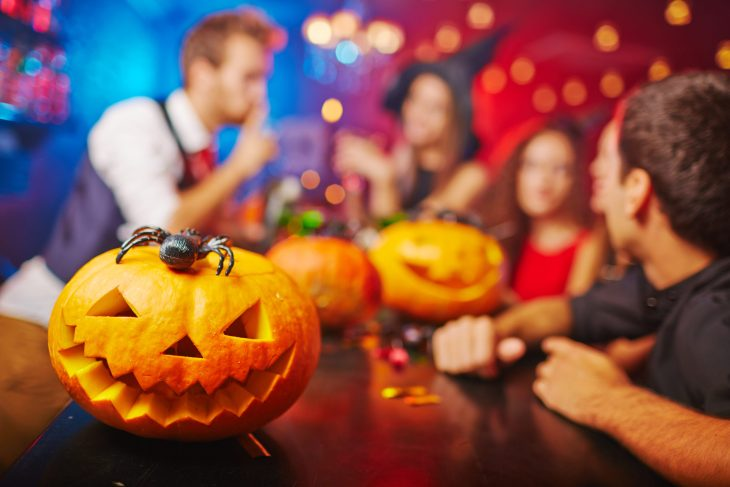 A jack-o-lantern with people having a costume party.