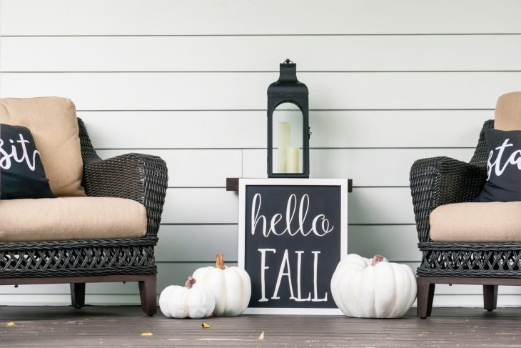 A porch decorated with a sign that say hello fall.