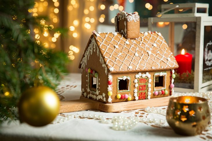 Gingerbread house stands in the middle of the frame surrounded by Christmas decorations.