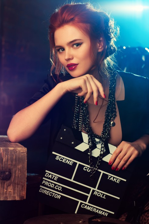 Red haired woman in black shirt and matching jewelry holding a film slate