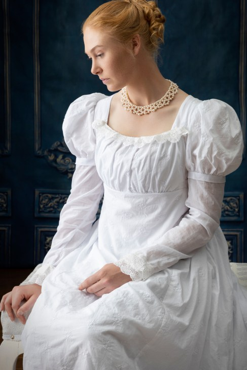 A red haired woman in a white regency style dress and filigree collar necklace