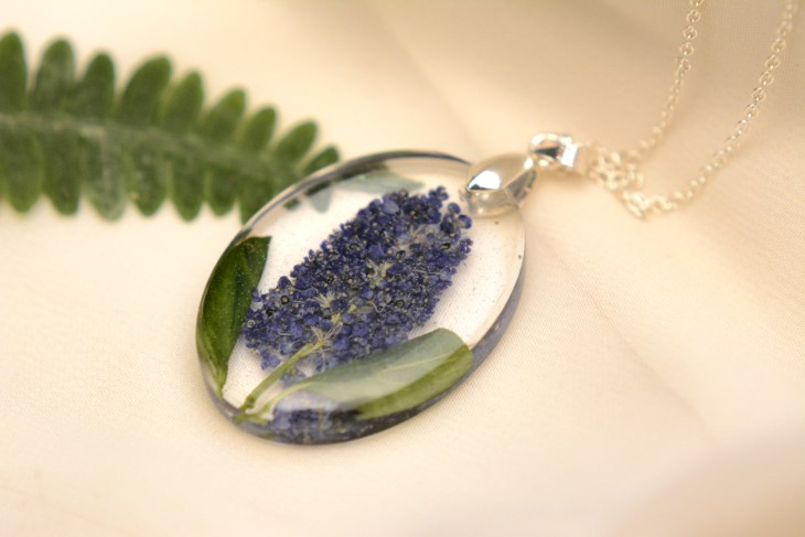 A resin pendant containing a purple flower