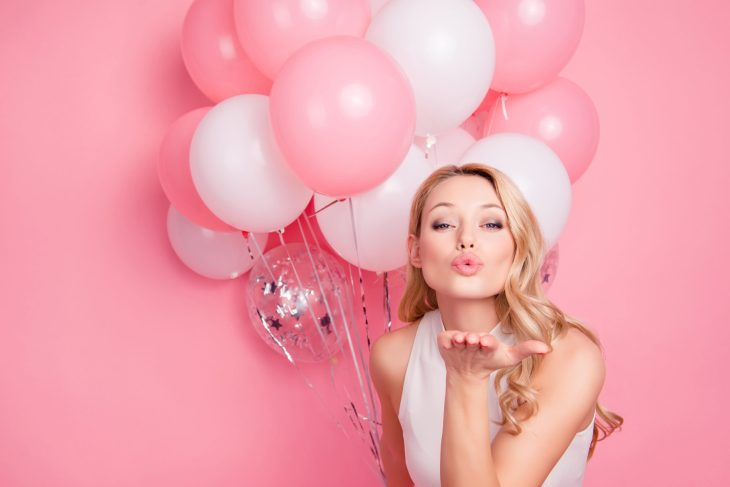 Blonde woman with pink and white balloons blowing a kiss
