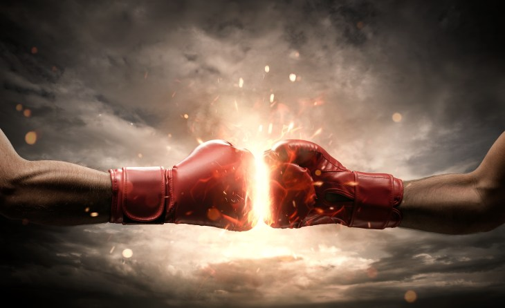 Red boxing gloves are powered together with fire in between them.