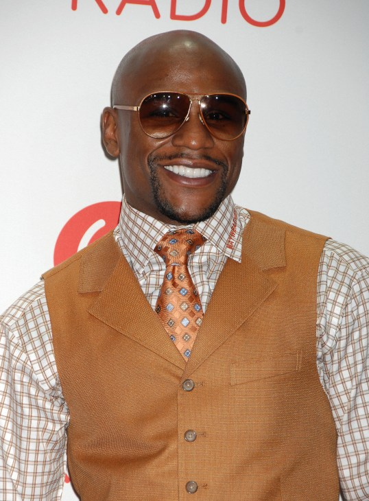 Floyd Mayweather Jr. is wearing shades and a white striped dressy shirt. Brown tie and a brown vest.