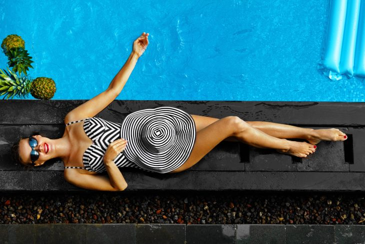 Beautiful tan woman in a swimsuit laying by the pool