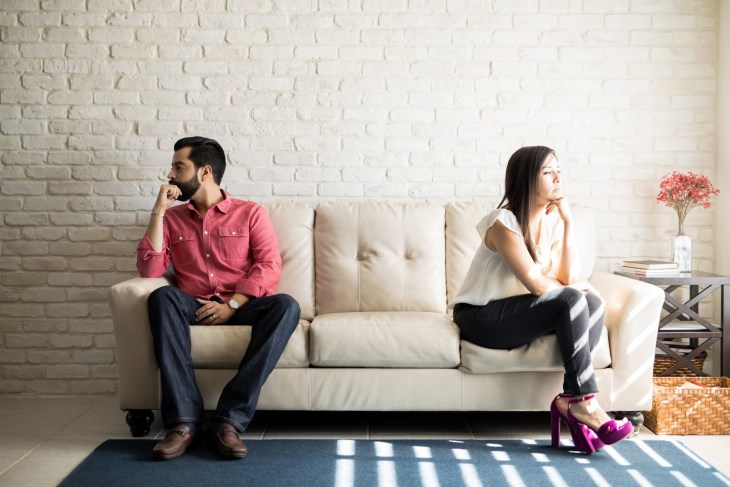 Couple being distant from each other on couch