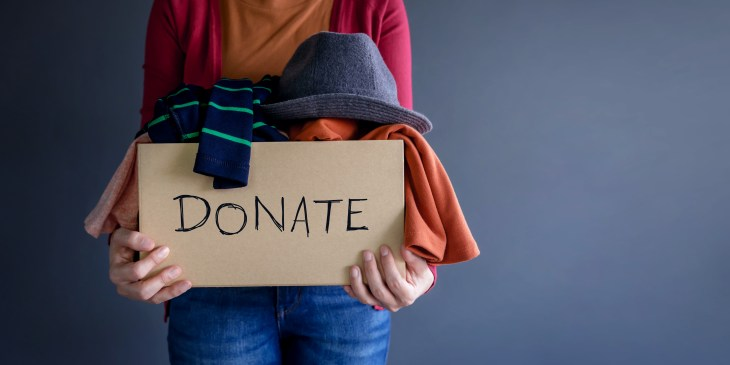 woman holding a donate box full of clothes