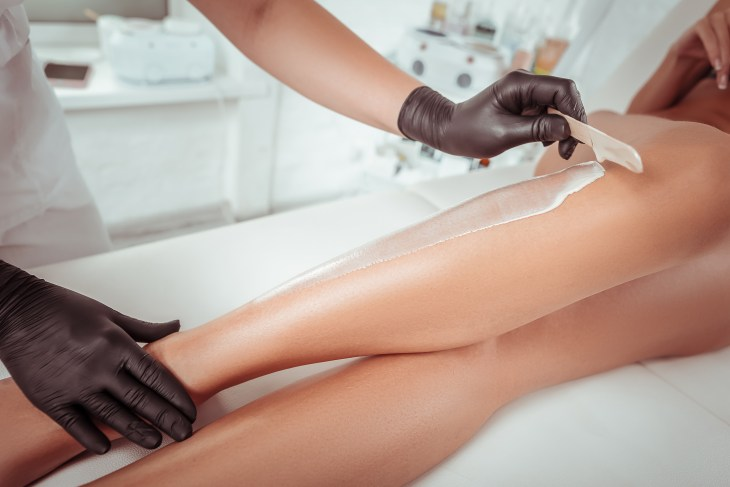 woman laying on a table getting her legs waxed