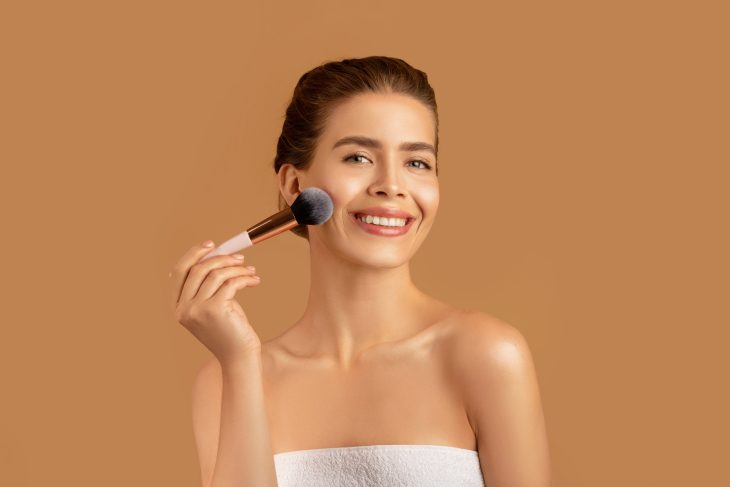 young woman in a towel putting on soft glam makeup, still looks natural but elevated