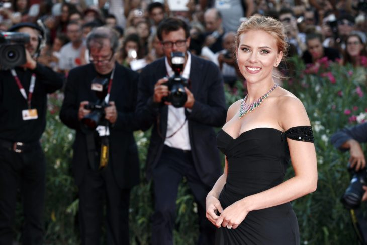 Scarlett Johanson at premier or red carpet getting professional pictures taken. In black off the shoulder dress with hair up looking stunning.