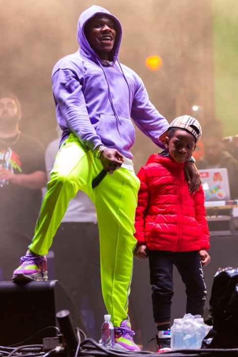 Dababy standing next to a child onstage at an event