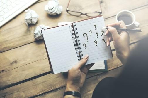 woman written question mark on notepad