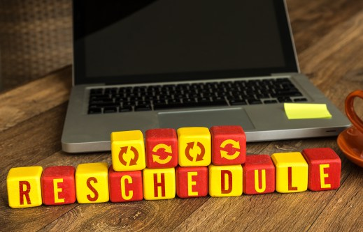 Reschedule written on a wooden cube in front of a laptop