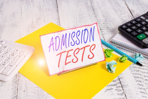 Writing note showing Admission Tests. Business photo showcasing an exam that you take to be accepted into a school Notepaper on wire in between computer keyboard and sheets.