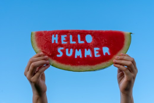 A piece of watermelon against a blue sky. Children's hands are holding a slice of watermelon with the text Hello Summer. Summer time concept