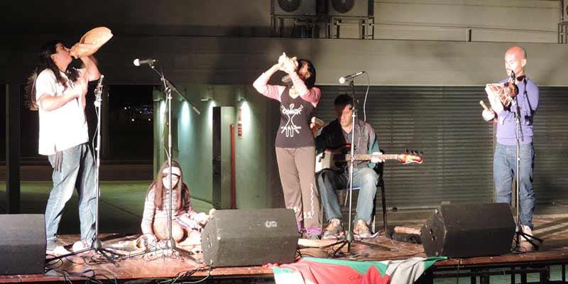 Ciro y el Clan Choñik en un escenario. A la izquierda, Ciro tocando un instrumento musical de viento tradicional, la caparzón de un caracol de mar, en el centro, sentada, una niña indígena tocando instrumentos de percusión, a la derecha, una compañera artista de Ciro tocando también un instrumento de viento, y a la derecha de ella, otro artista tocando un instrumento de percusión, al fondo acompaña un músico tocando el bajo sentado.