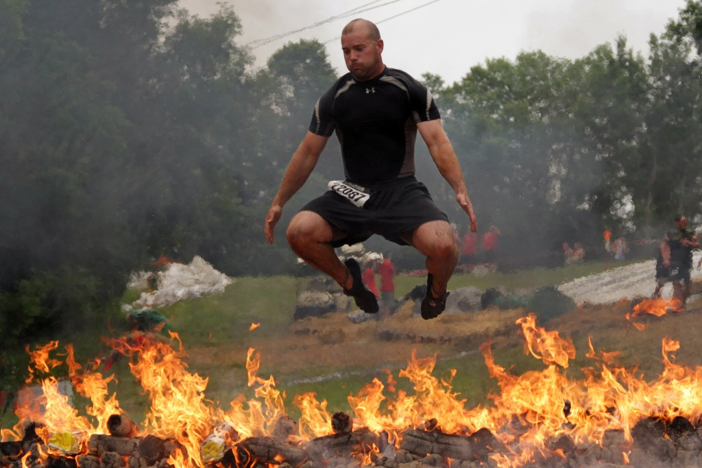 man jumping over flames
