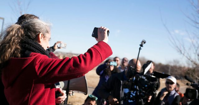 """Immigrant rights activist Jennifer Piper holds up her cell phone to the crowd, so that Jeanette Vizguerra can hear: """"Your people are with you."""" (Photo by Allen Tian)"""