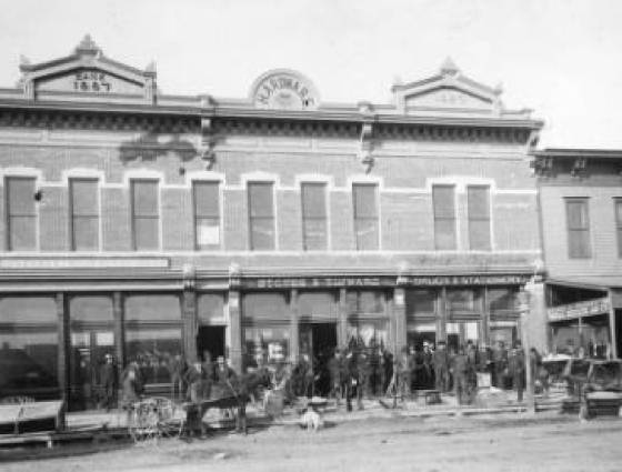 Lamar- Citizens stand outside a commercial block that includes a bank, hardware, drugs & stationery and real estate, 1890