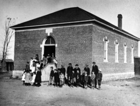 Arvada - Early brick school, 5650 Wadsworth Blvd.  Teacher, Miss Nettie E. Stilling, is shown with students, 1880