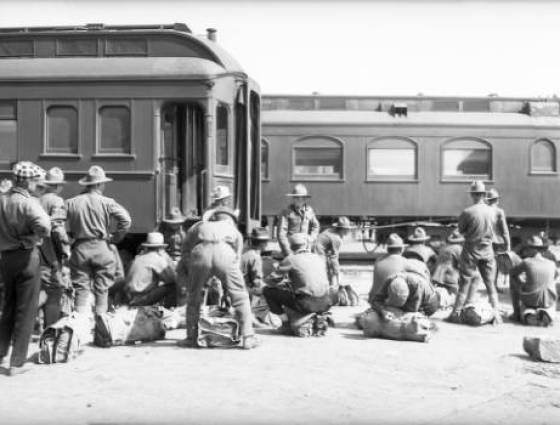 Soldiers wait to board the Denver and Rio Grande passanger train cars ready to depart from Fort Logan - 1917-1918.