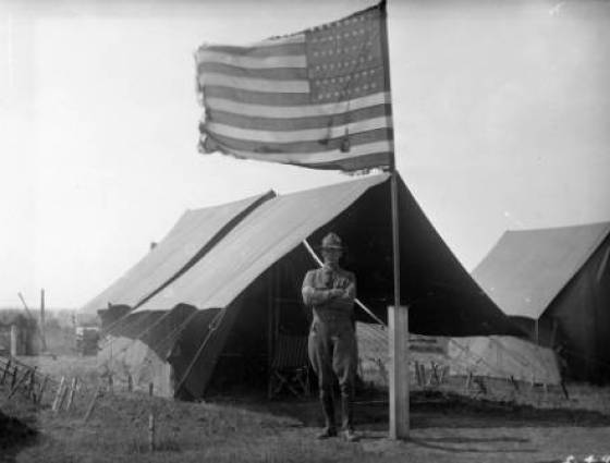 A soldier, in uniform, poses outside a staked walled tent beside a flag pole with a fringed American flag - 1917.