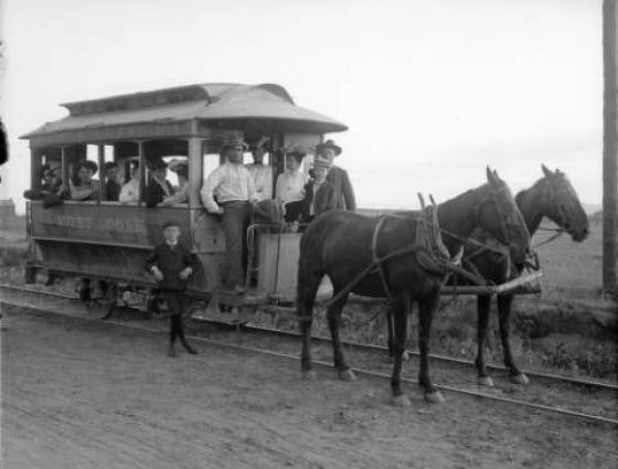 A rail car, drawn by a two horse team, is carrying men, women, and children on the Fort Logan rail line - 1890-1900.