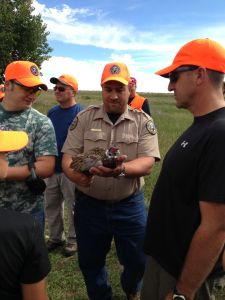 Theo Stein, hunter and angler outreach coordinator for CPW's Northeast Region, holds a rooster pheasant.