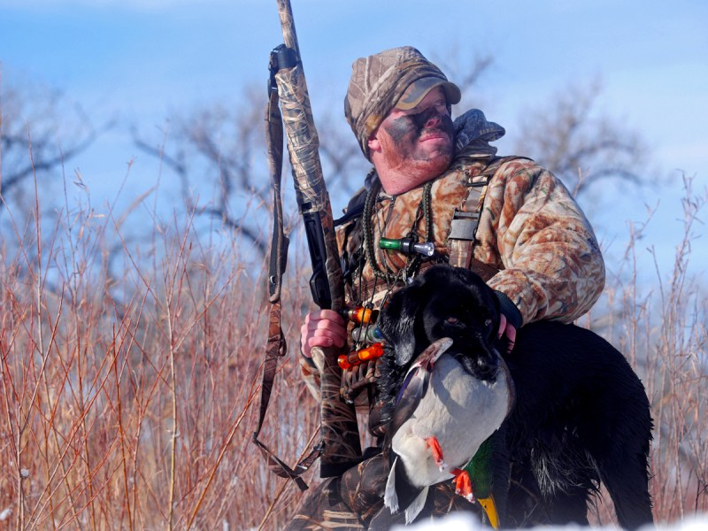 Hunter Brian Marsh and a black Lab with a duck