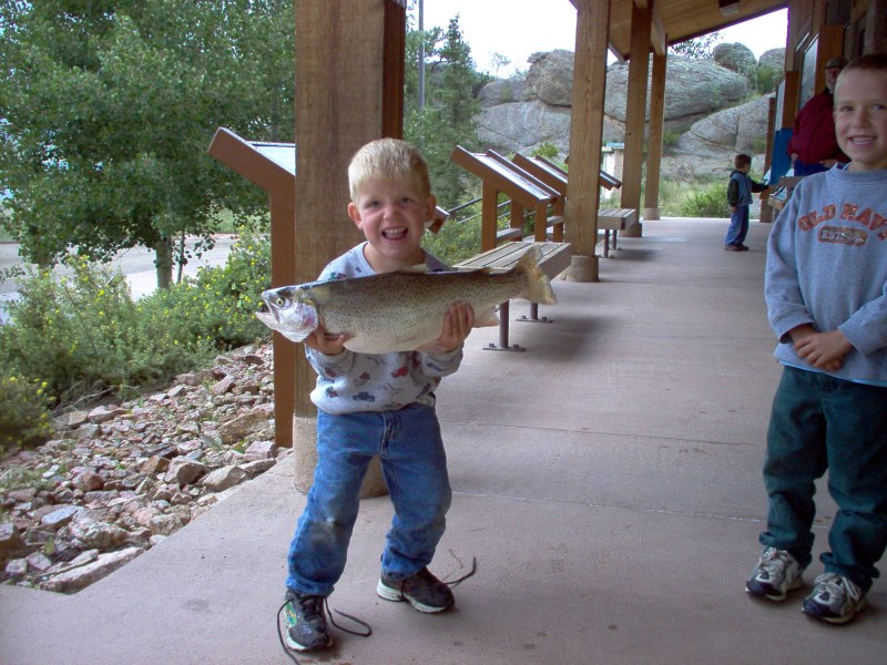 A young angler poses proudly with an Eleven Mile Reservoir rainbow trou