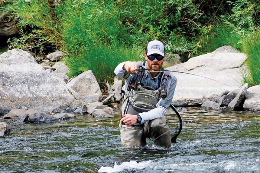 angler fighting fish in river