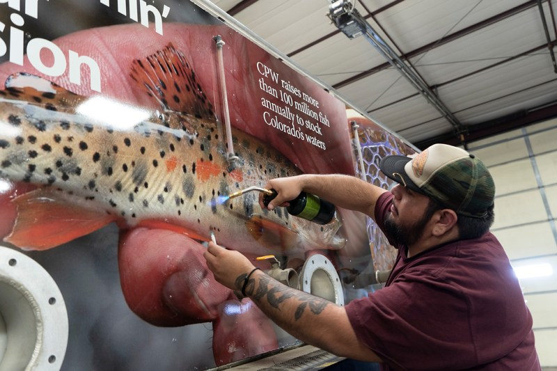 Using torch to apply vinyl wrap to CPW hatchery truck
