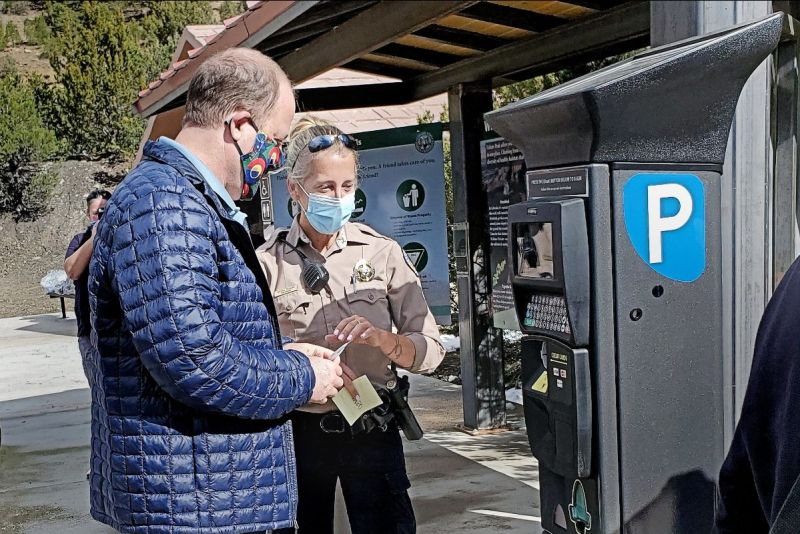CPW Park Manager Crystal Dreiling discusses with Gov. Jared Polis the process of buying a park pass from a solar-powered kiosk in the parking lot of Fishers Peak State Park at the Sneak Peek opening event. Courtesy of Colorado Parks and Wildlife / Bill Vogrin